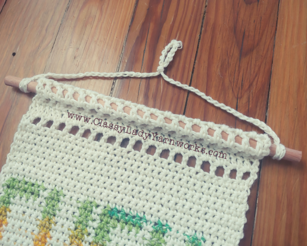 Close up of the top border of a crocheted wall tapestry that shows the double crochet stitches used to create the border.