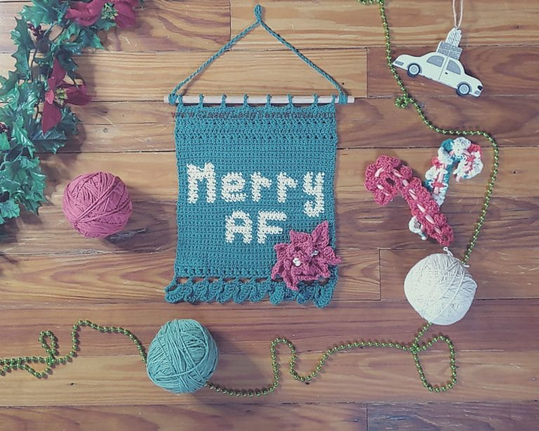 """Finished example of a crochet pattern that says """"Merry AF"""" surrounded by various ornaments and balls of yarn in green, red and white. Represents a crochet pattern available at Classy Lady Yarnworks"""