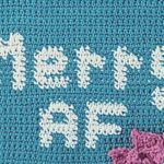 """Close up of graph section of crochet wall hanging that says """"Merry AF"""" Represents the graph section of the pattern."""